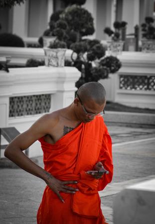 A Thai monk with his smartphone at the famous Wat Arun Ratchawararam Ratchaworamaha Wihan in Bangkok, Thailand