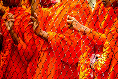Young Cambodian monks stand behind a demarcation and wait hopefully