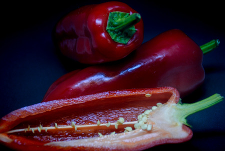 a red pointed pepper cut half in half makes a beautiful contrast to the black background
