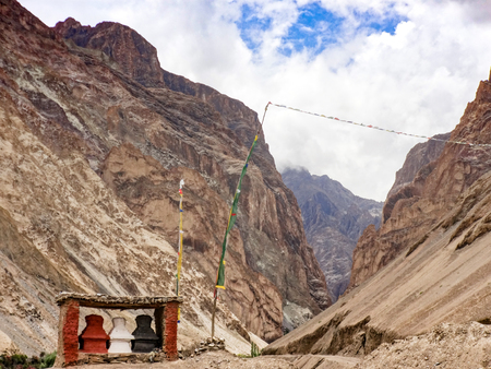 Three small black and red gompas stand at the beginning of a mountain route through two rocks. India