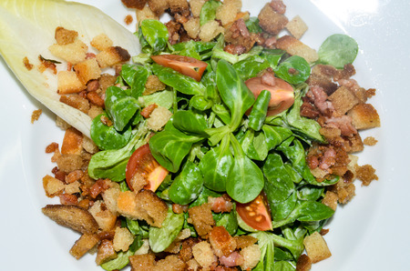 A deliciously prepared lambs lettuce with roasted pieces of bread and cherry tomatoes slices