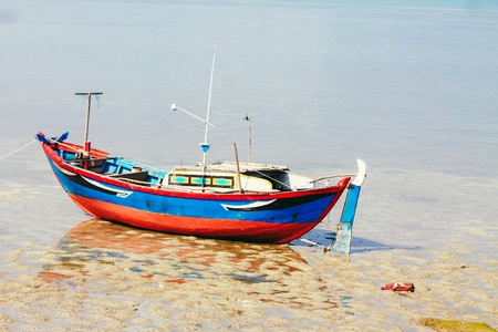 A small red blue Vietnamese fishing boat is lying on the beach. The beach is soon covered by the tide Stock Photo