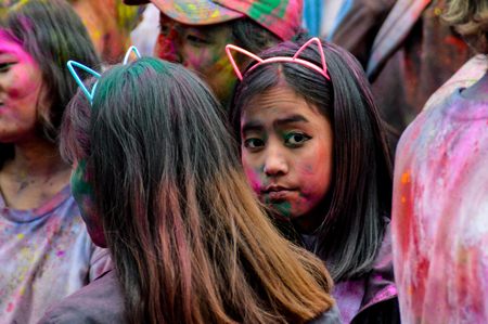 A portrait of a colored powdered Nepalese girl at the Holi Festival in Pokhara, Nepal