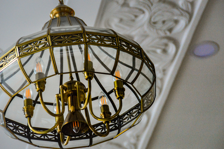 A golden chandelier hanging from a stucco house ceiling