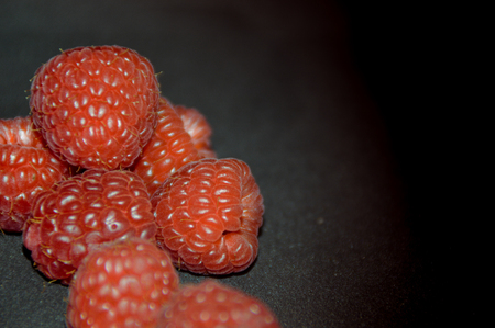 A close-up of arranged red raspberries on black background