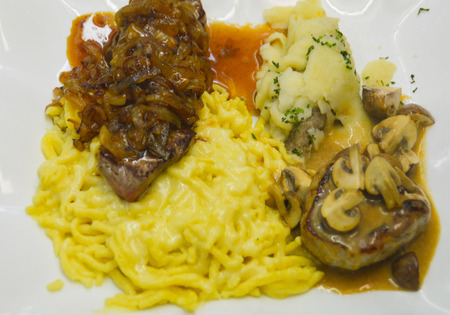 This Swabian court comes from the south of Germany. It consists of a ravioli, spaetzle topped with cheese, fried onion in a sauce, a pork medallion and a pork steak