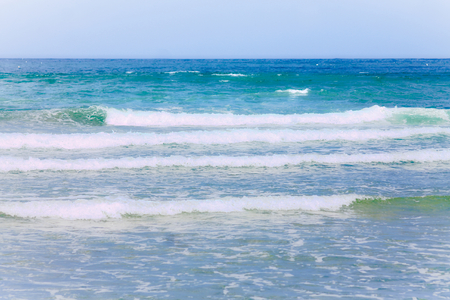 A background image from a white, light blue colored coastline to a deep blue horizon