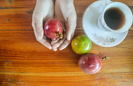 Coffee and passion fruit, how can the day start better? A passion fruit is held in two hands