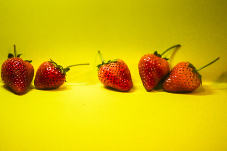 Red fresh strawberries on yellow background arranged in a row