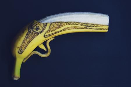 Handgun made of a banana on a black background. Stok Fotoğraf