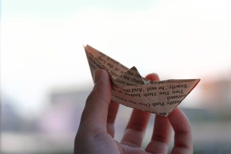 folded paper boat, showing concept of chasing dreams, aspiration, travel and goals