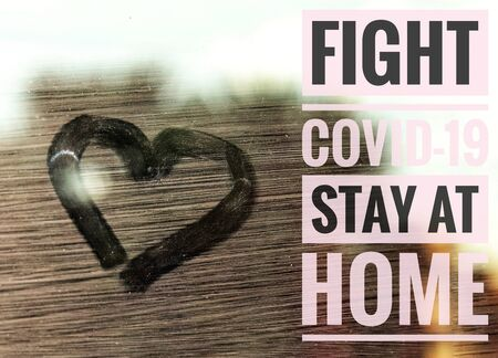 """Heart shape traced on a window glass and """"Fight The Spread of Covid-19 Stay Home"""" written in order to raise awareness of the global pandemic"""