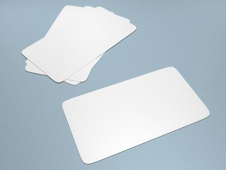 A set of blank business cards against a light blue background Foto de archivo