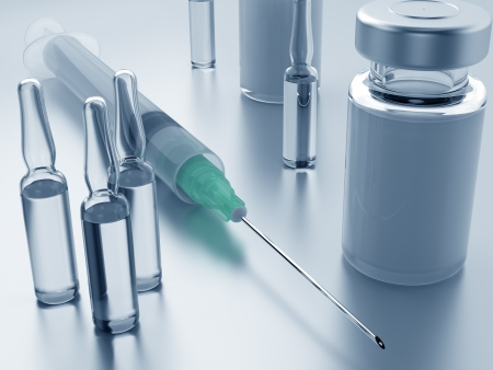 Ampules, bottle and syringe needle on a metal surface photo