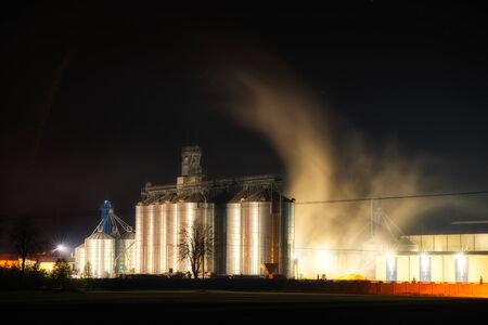 Grain dryer plant working at night with steam floating around it. The agro farm metal elevator, tall silo with dark sky on the background.