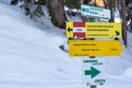 Yellow Tourist Directional Signs. Information to visitors about paths, attractions, distances and points of interest. Schladming Dachstein, Styria, Austria, Europe Stock Photo - 135052588