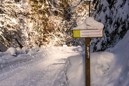 Snow-covered wooden road sign with warning text in German and English: Mountain bikers Please slow down. Sunny day, walking path in winter scenery.