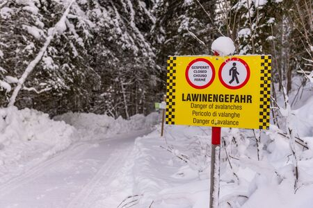 Yellow-black warning sign and signs in German, English, Italian and French: Closed, Danger of avalanche. A forest, snow-covered road in the mountains. Styria, Austria, Europe Stock fotó