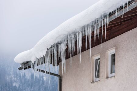 Big icicles hanging over the rain gutter on a roof of a traditional wooden house in the mountains in winter could be dangerous. Banco de Imagens