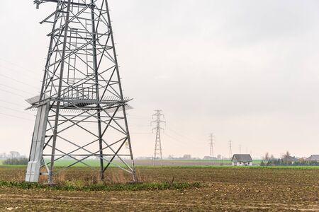 Système de distribution d'électricité. Ligne électrique aérienne à haute tension, pylône électrique, tour en treillis d'acier debout sur le terrain. Ciel bleu en arrière-plan. Banque d'images