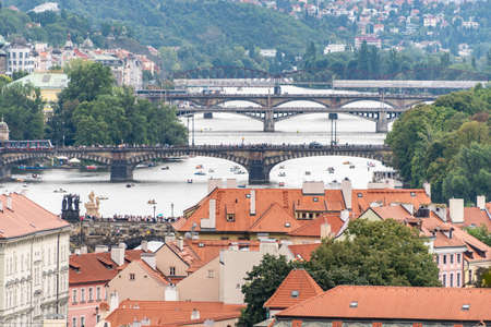 Above view at the cityscape of Prague and bridges over river Vltava on a sunny day. The detail view of modern and old part of town with traditional red rooftops.