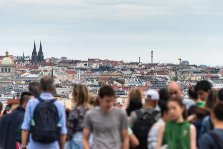 People, tourist watching cityscape of Prague on sunny day. The detail view of modern and old part of town with traditional red rooftops. Sajtókép