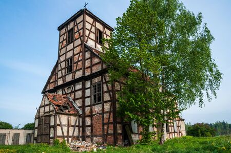 Ruins of the abandoned evangelical church made as half-timbered house with wood and red bricks. Blue sky and green grass and tree. Stock fotó