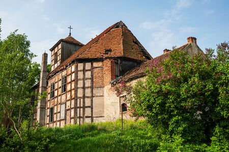 Ruins of the abandoned evangelical church made as half-timbered house with wood and red bricks. Blue sky and green grass and tree. Stock Photo