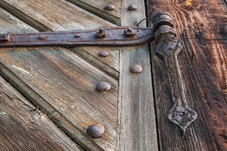 Close-up of an old, corroded and rusty hinge holding the wooden door. Details of wood and metal structure and soft focus. Stock fotó