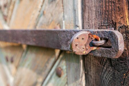 Close-up of an old, corroded and rusty padlock closing the wooden door. Details of wood and metal structure and soft focus. Stock fotó