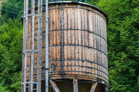 The wooden water supply tank on the background of green trees. The tank is placed on a wooden structure with pipes and a ladder attached to it.