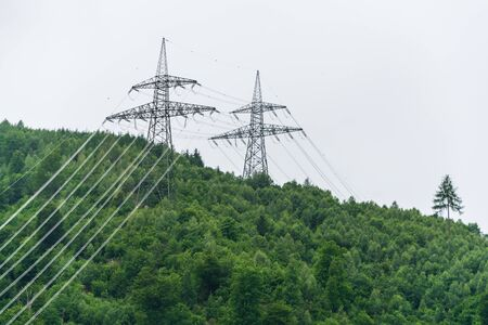 High voltage overhead power line, power pylon, steel lattice tower standing in the Austian mountains landscape. Electricity distribution system in Austria.