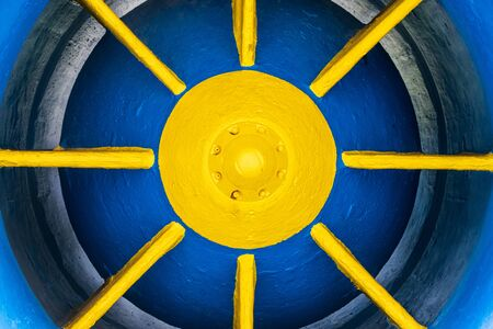 Close-up of a piston valve, painted in yellow and blue. A metallic element in the construction of a hydroelectric power plant.
