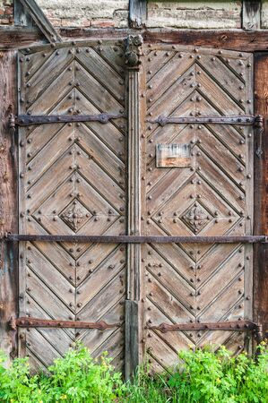 Old wooden door decorated with carved wood made flowers with corroded and rusty fittings and hinges. Details of wood and metal structure and green grass below.