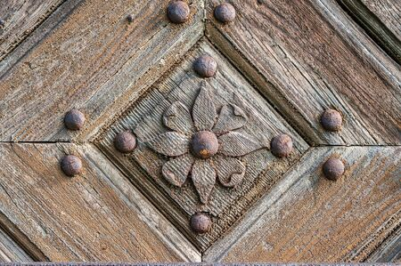 Close-up of an old wooden door decorated with carved wooden flowers with corroded and rusty fittings and hinges. Details of wood and metal structure. Stock fotó