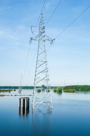 The high voltage power lines on water. Blue sky and green trees during river flood via pylon tower. Sunny spring day. Stock fotó