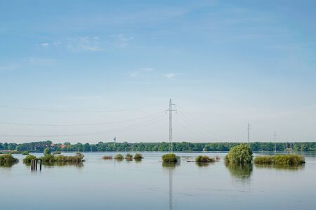 The high voltage power lines on water. Blue sky and green trees during river flood via pylon tower. Stock fotó