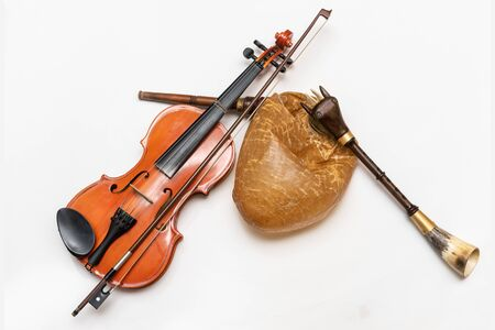 Violin and bagpipes, a traditional musical instrument. Bagpipes are a woodwind musical instrument from the group of reed aerophones (pipe aerophone). Close-up and white background.
