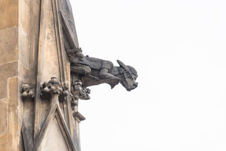Prague, Czech Republic - August 17,2019: Close up view of gargoyle in the Cathedral church Sacred Vitus. The gargoyle is a highly decorative spout, allowing water to be channeled away from buildings.