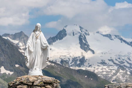 White statue of Virgin Mary, Mother of God, placed on top of the mountain. In the background there are snowy peaks of high mountains, blue sky, white clouds.
