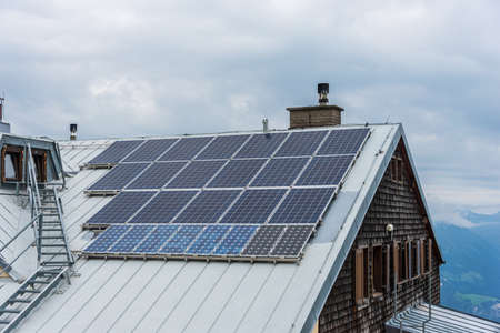 Solar photovoltaic panels PV on a house roof and chimney. Electricity from the sun during winter. House in the mountains with sky at the background.