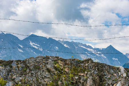 Barbed wire separating the mountain landscape. In the foreground there are solid stones and mountain plants, flowers. In the background high mountains, white clouds and blue sky.