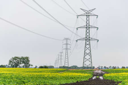 Extra-high voltage 400 kV overhead power line on large pylons, used for long distance, very high power transmission. Cloudy sky and green field.