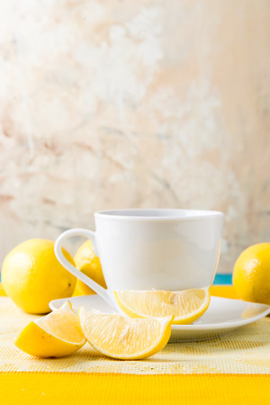 Cup of coffee  hot tea drink  beverage with sliced and whole lemons on yellow placemat table setting Stock Photo