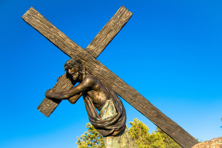 cross: Historic landmark located in San Luis Colorado, near the New Mexico Border. This historic statue depicts Jesus Christ carrying the cross to his crucifixion. Locals and tourists travel to this location and place religious rosary beads on and near the statu Stock Photo