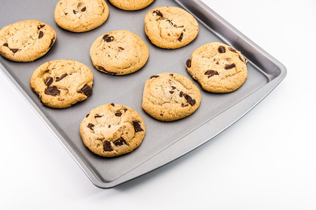 cookie sheet: Freshly Baked Chocolate Chip Cookies out of the oven - on cookie sheet on white background