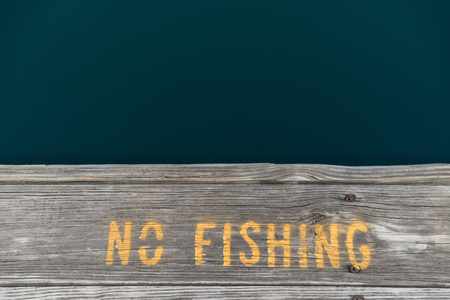 boat dock: No fishing warning sign on the deck by a boat dock.