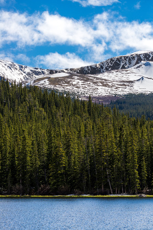nature landscape of mount evans taken from echo lake in colorado. snow covered mountains .. snow capped mountains and green pine tree forest.
