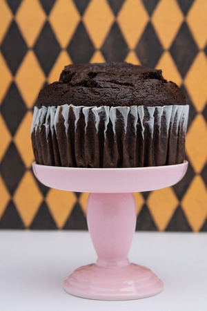 a chocolate muffin on a pink dessert stand pedestal against a  fun background in a dessert shop.