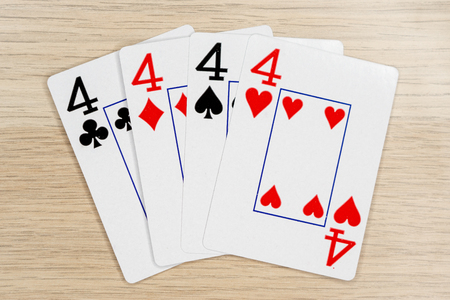 4 of a kind fours 4  - winning hand of gambling casino poker playing cards on a table.